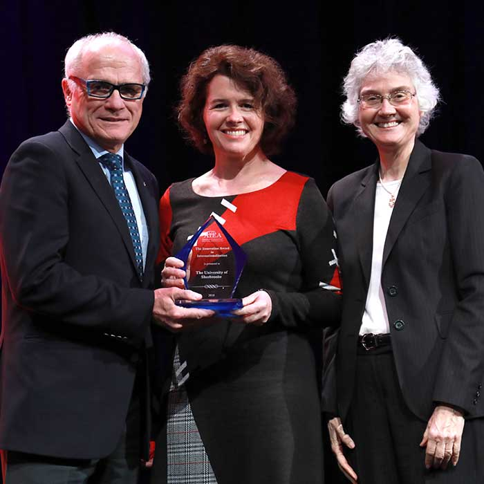 Nell Pynes gives award to two representatives from the University of Sherbrooke.