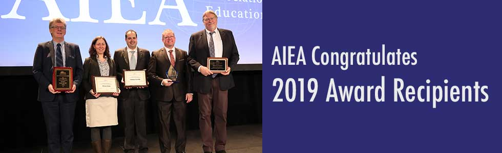 Text: AIEA congratulates 2019 award recipients. Photo: 2019 award recipients with their awards on stage at conference